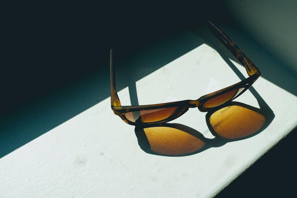 brown framed sunglasses on white surface
