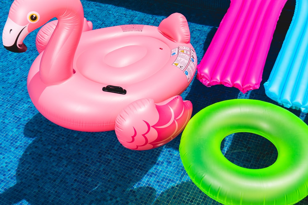 pink inflatable flamingo and green inflatable ring