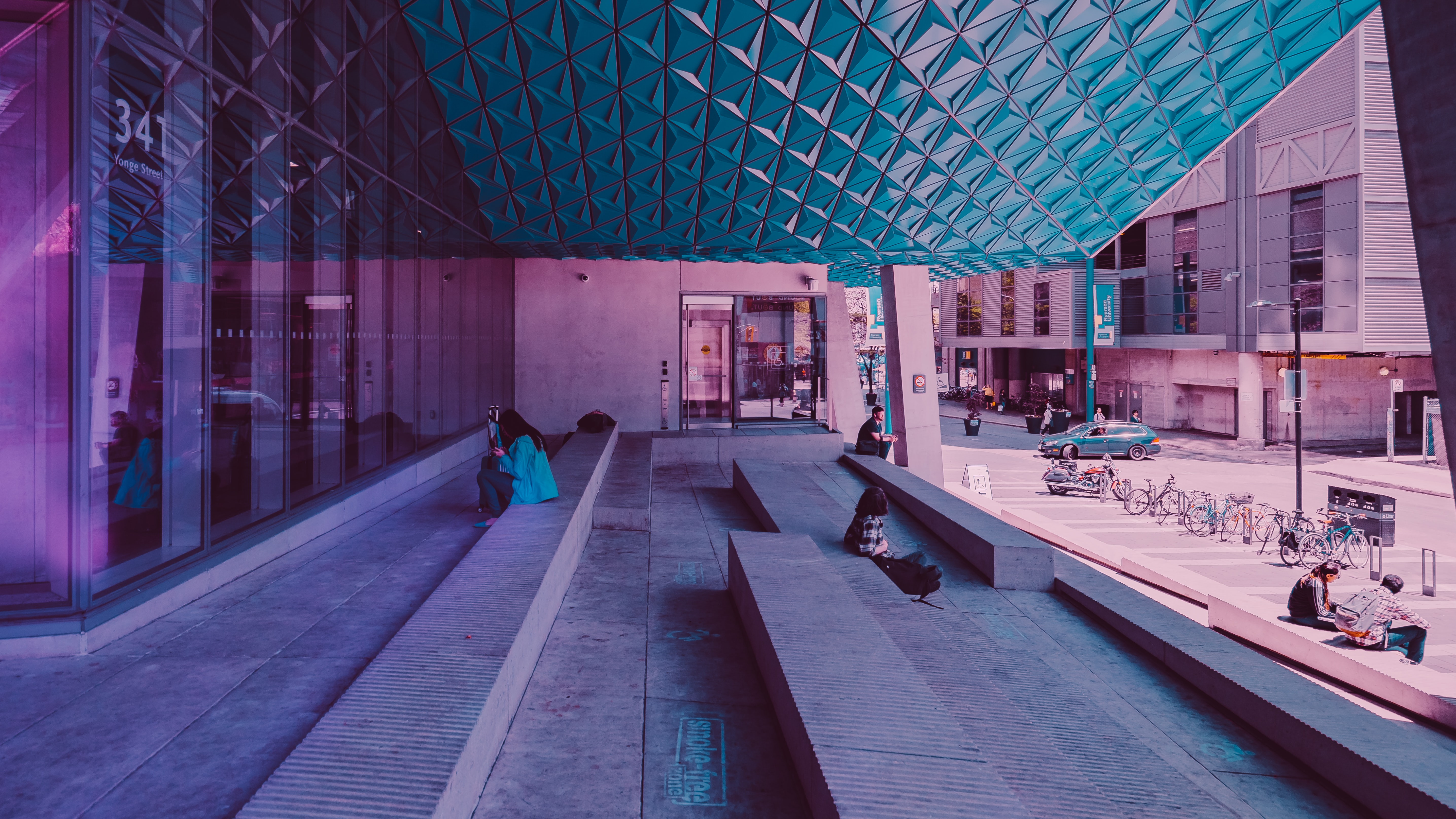 woman sitting on sidewalk near building