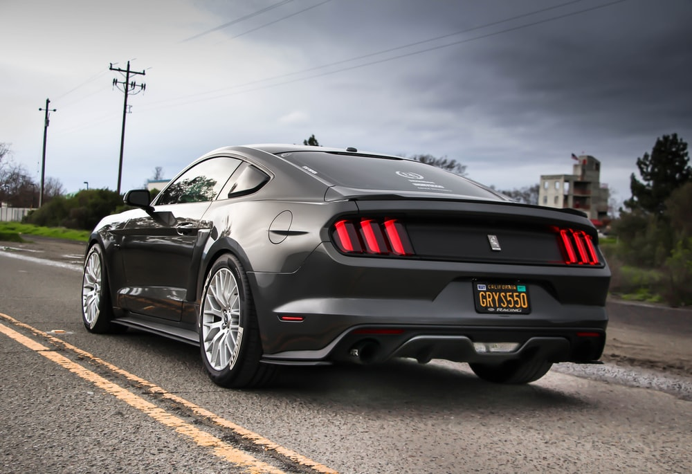 shallow focus photography of black Ford Mustang GT on the road