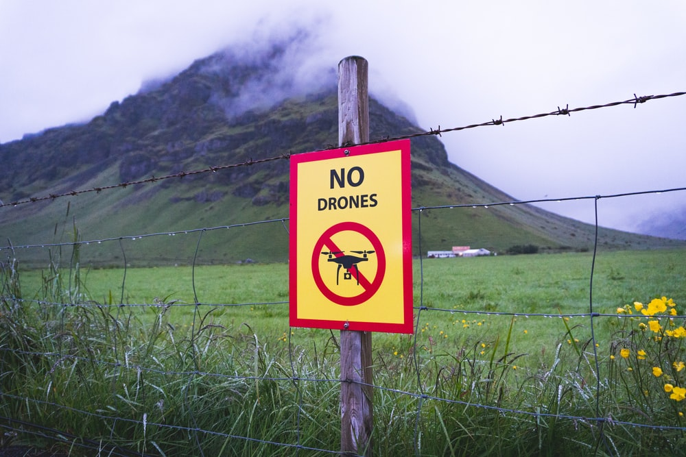 no drones signage on brown wooden post across mountain with fogs