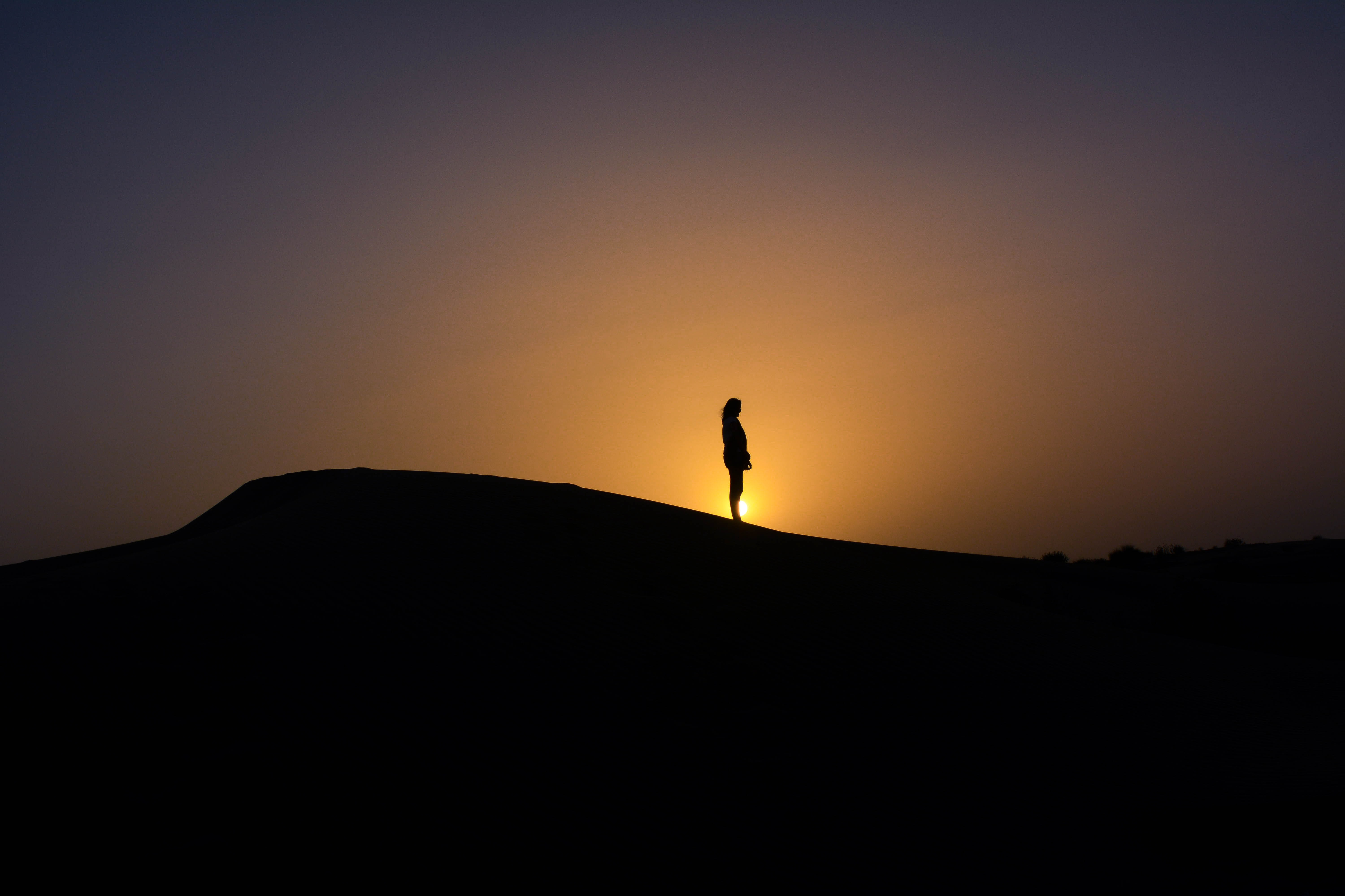 silhouette of person standing on mountain with sunset sun