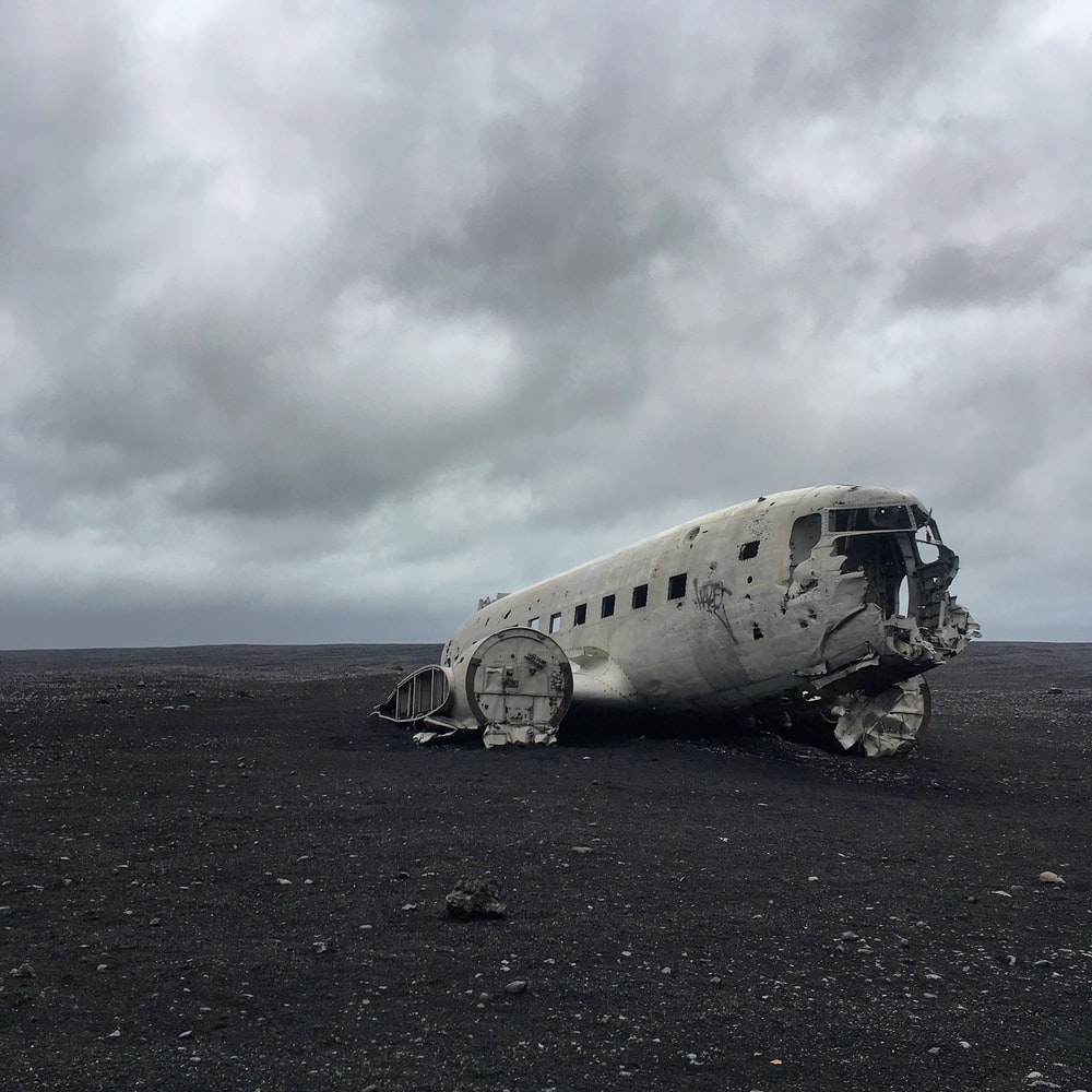 wrecked gray airplane on brown soil under gray clouds during daytime