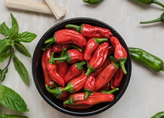 close-up photography of red bell peppers surrounded by green bell peppers