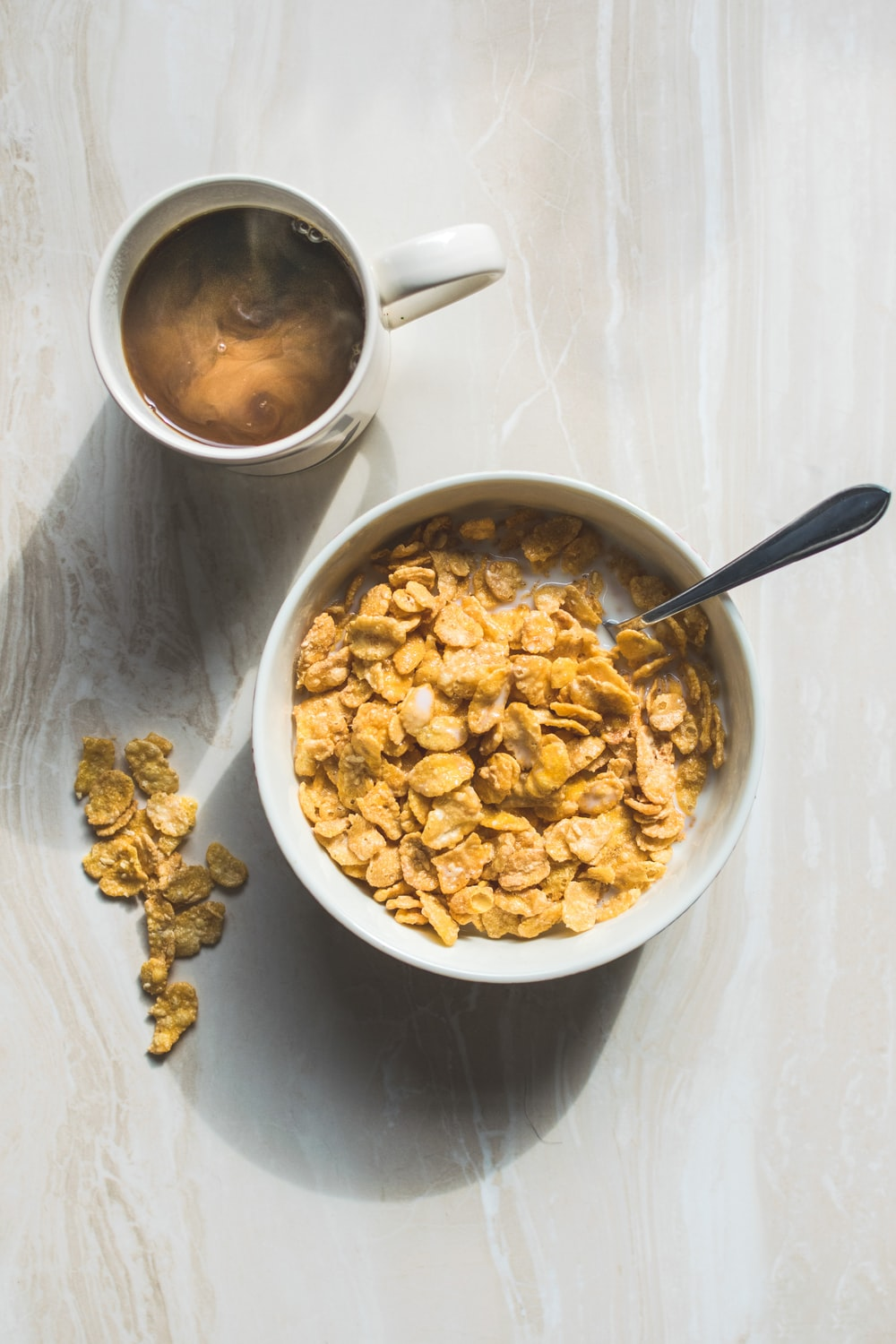 ceramic bowl filled with cereals and spoon