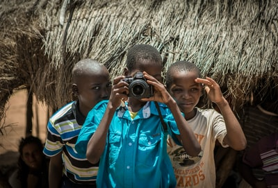 two boys standing behind boy using camera mozambique zoom background