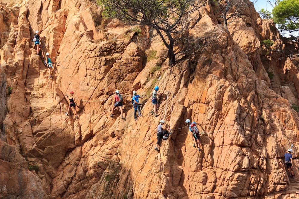 people climbing mountain under sunny sky