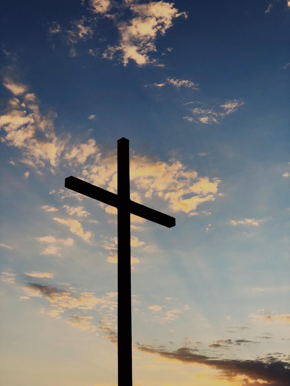silhouette of cross under blue sky