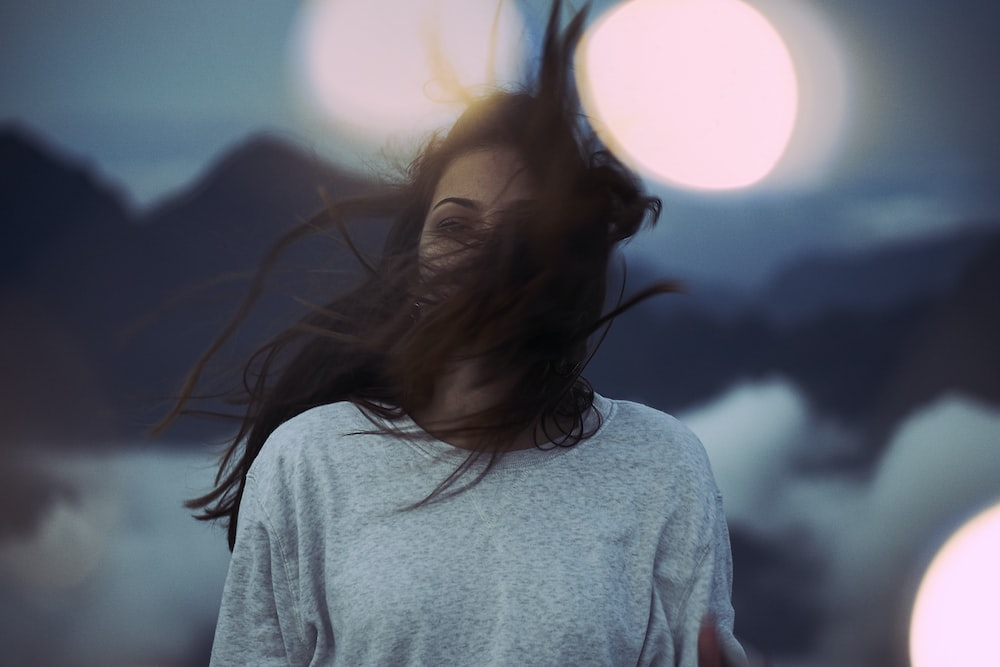 shallow focus photography of woman with hair covering her face