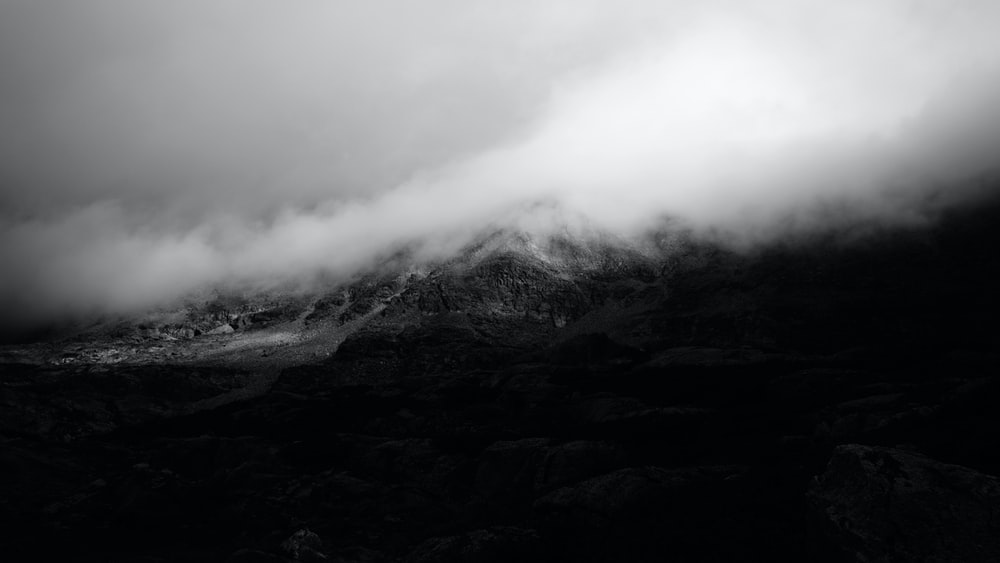 grayscale photo of mountain covered by clouds