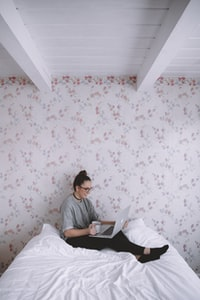woman holding white ceramic cup while using laptop