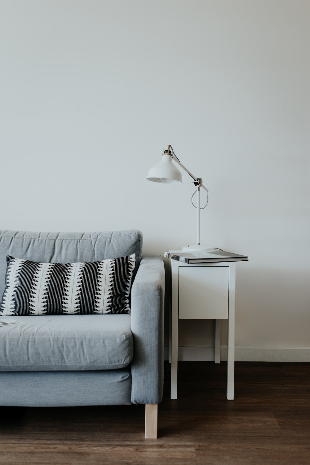 white study lamp on top of white wooden end table beside gray fabric sofa