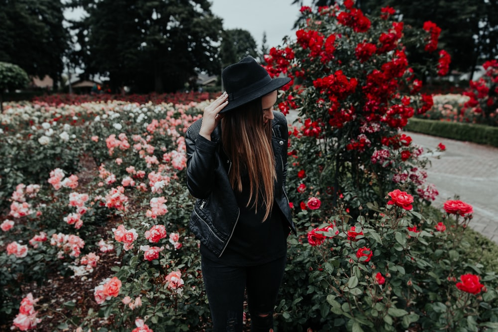 woman in black suit jacket and hat near field of pink and red roses