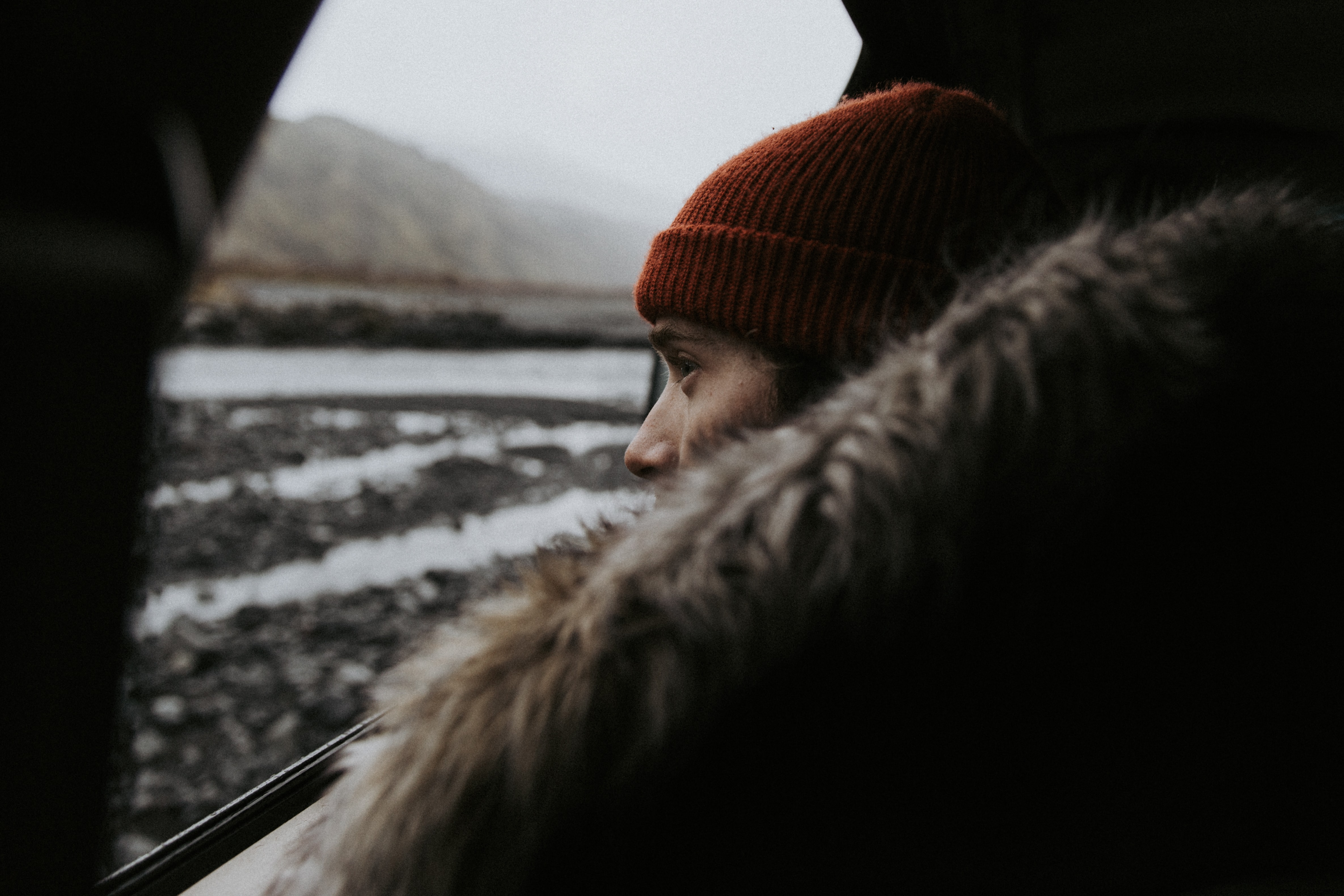 shallow focus photography of woman starring outside the window