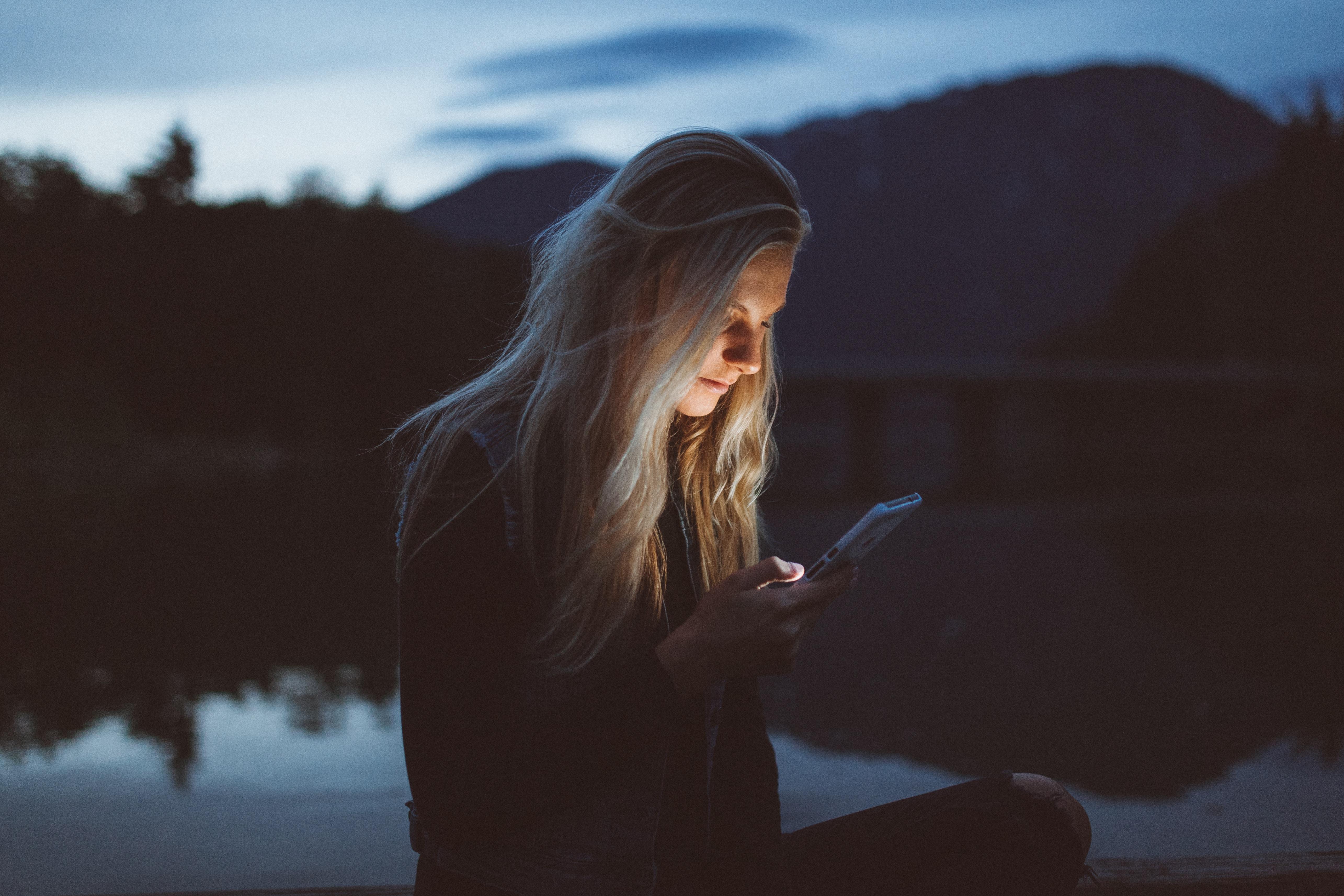 Compartir todo en las redes sociales, chica con el celular  en la montaña