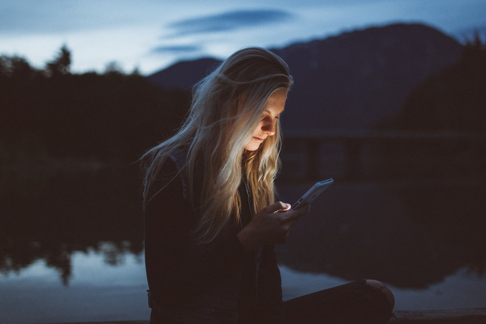 woman looking at phone beside body of water