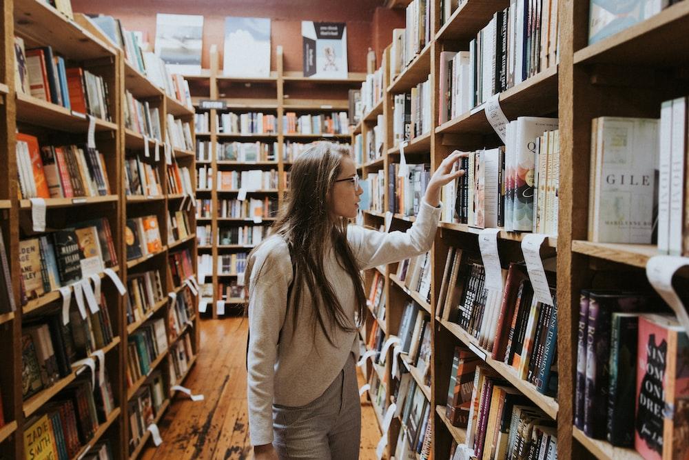woman holding book on bookshelves