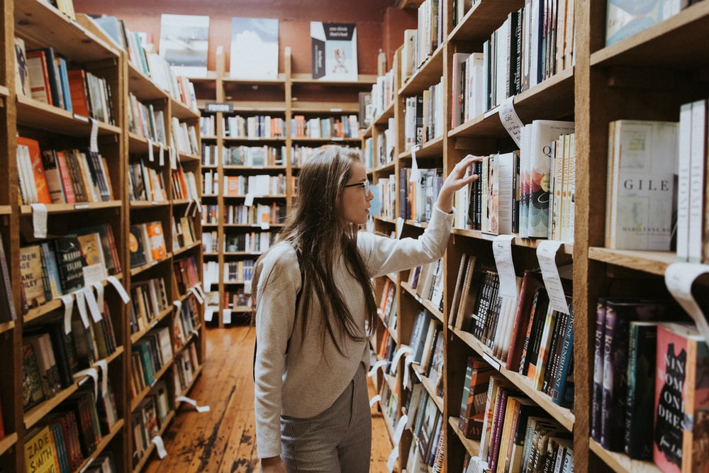 woman holding book on bookshelves