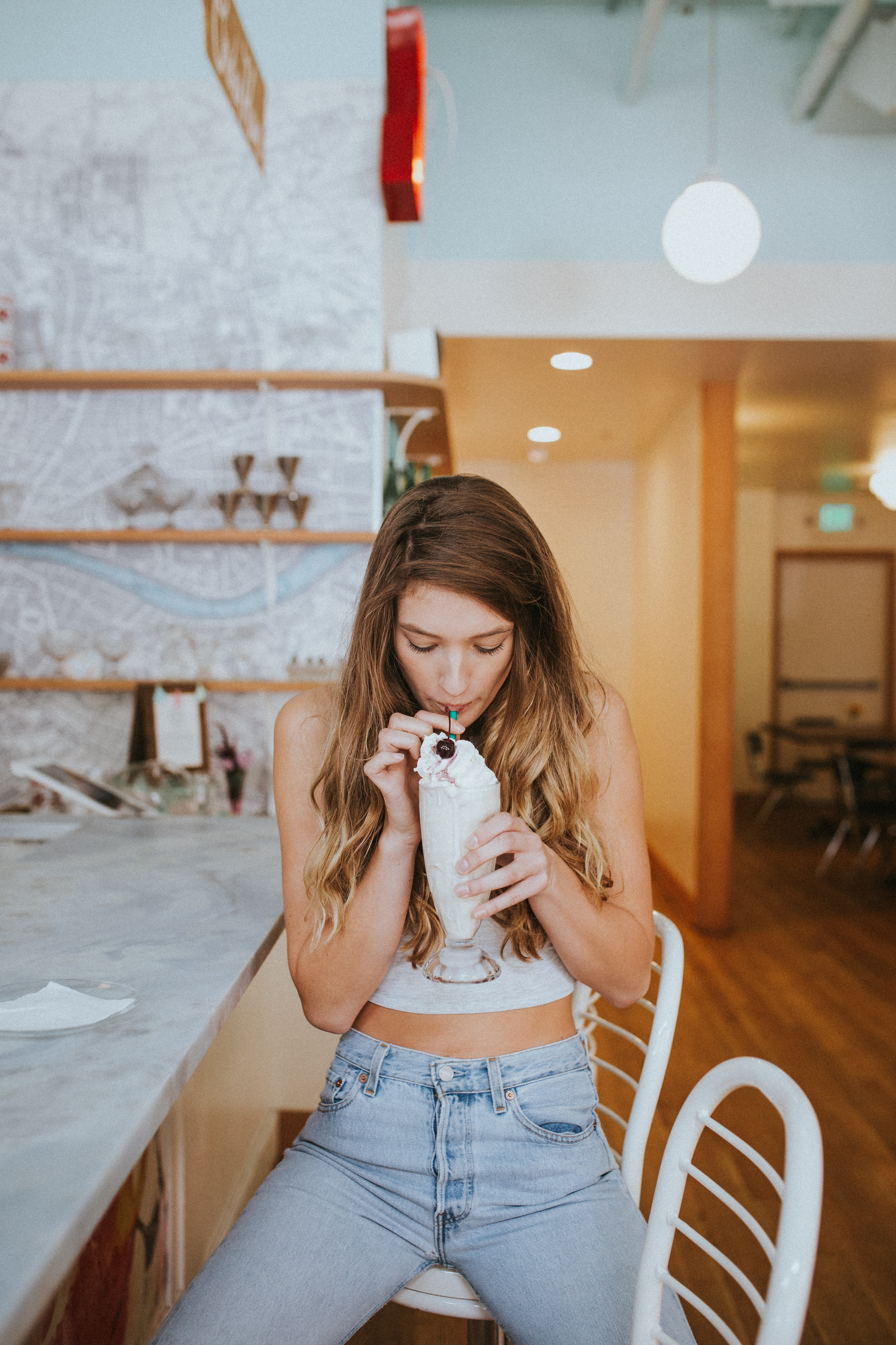 woman zipping ice cream float while sitting on chair inside room with lights turned on