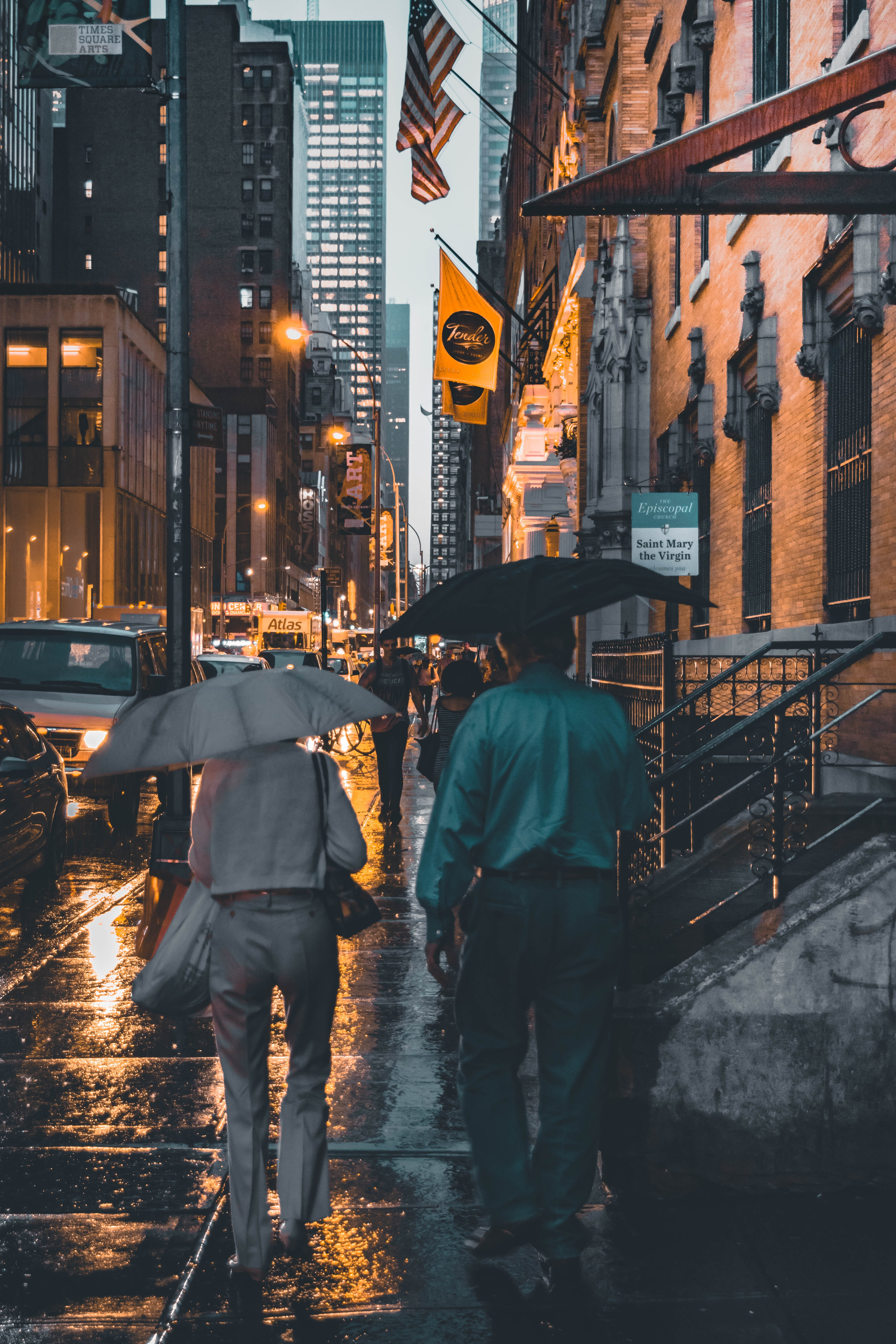 two man and woman walking near each other while holding umbrella during rain near buildings