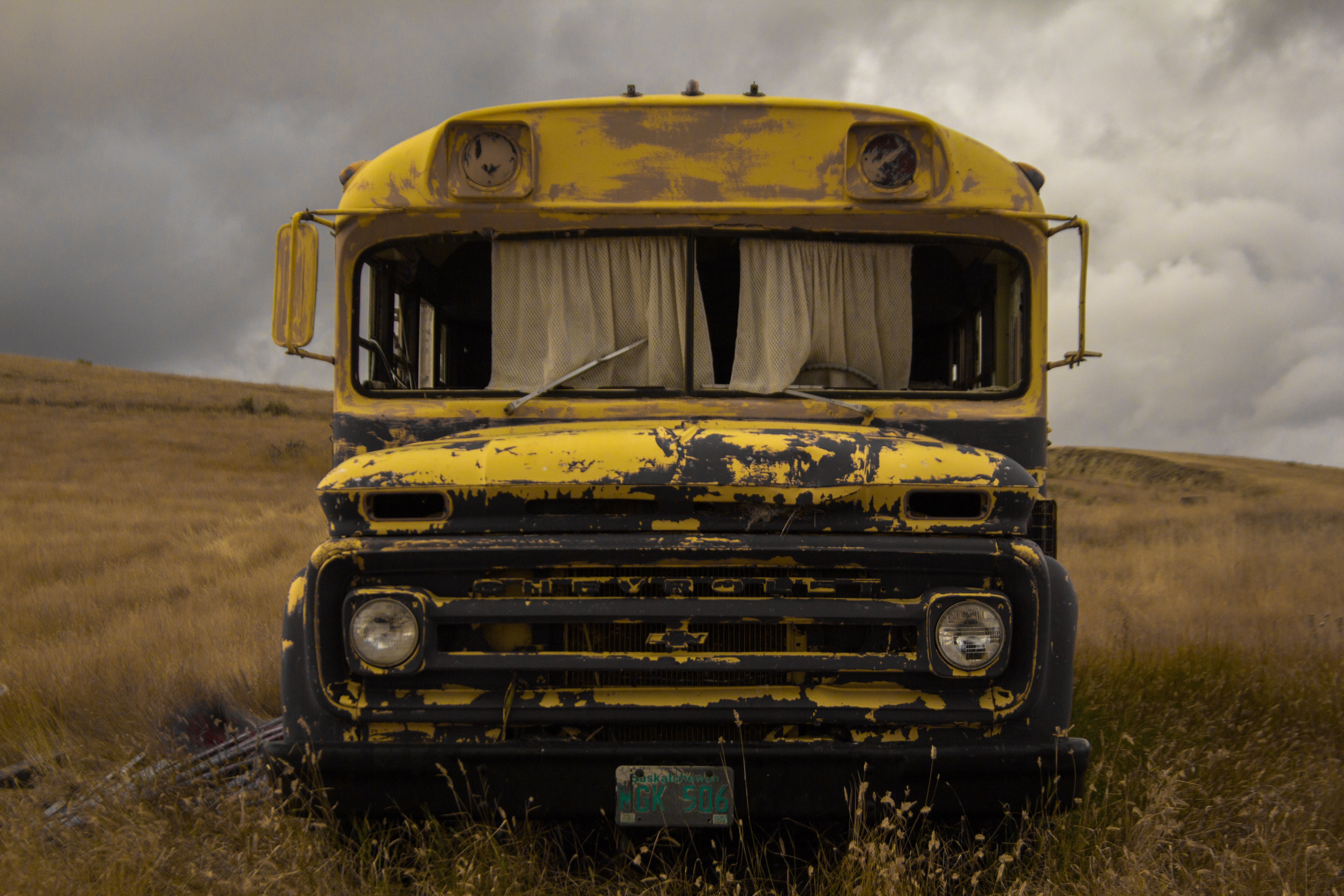 abandoned yellow school bus on green grass field during daytime