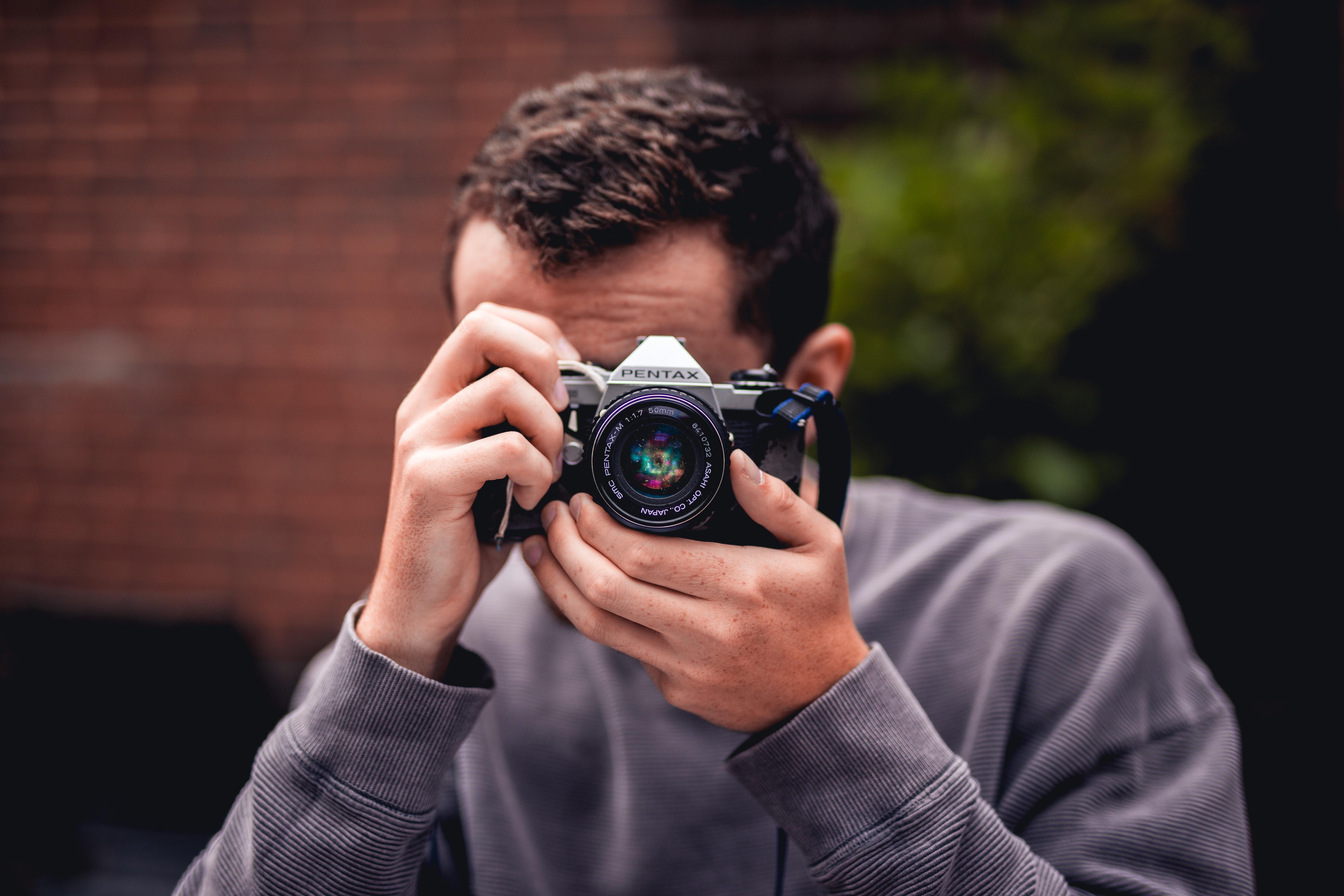 person taking photo using Pentax DSLR camera