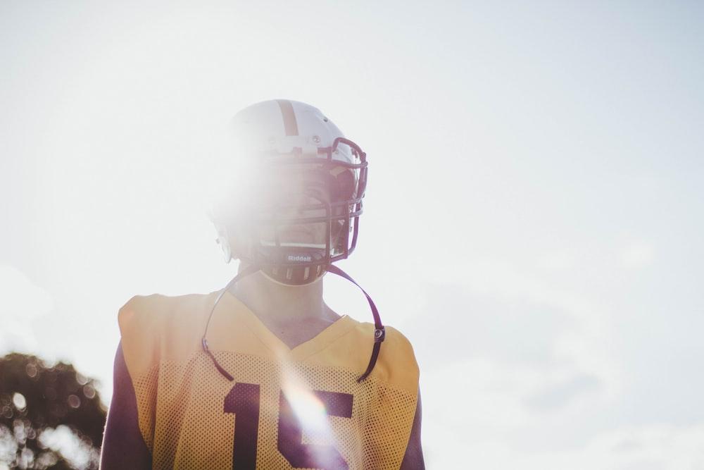 man wearing yellow jersey shirt and white helmet