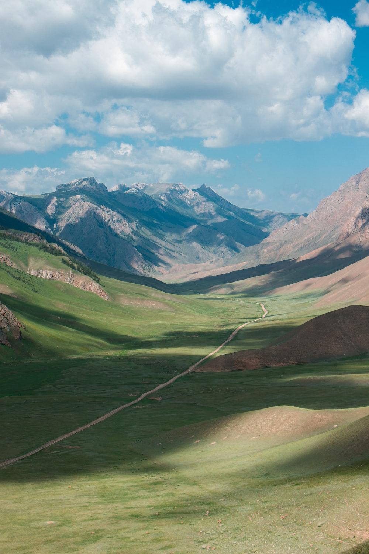 green grass field valley under white clouds during daytime