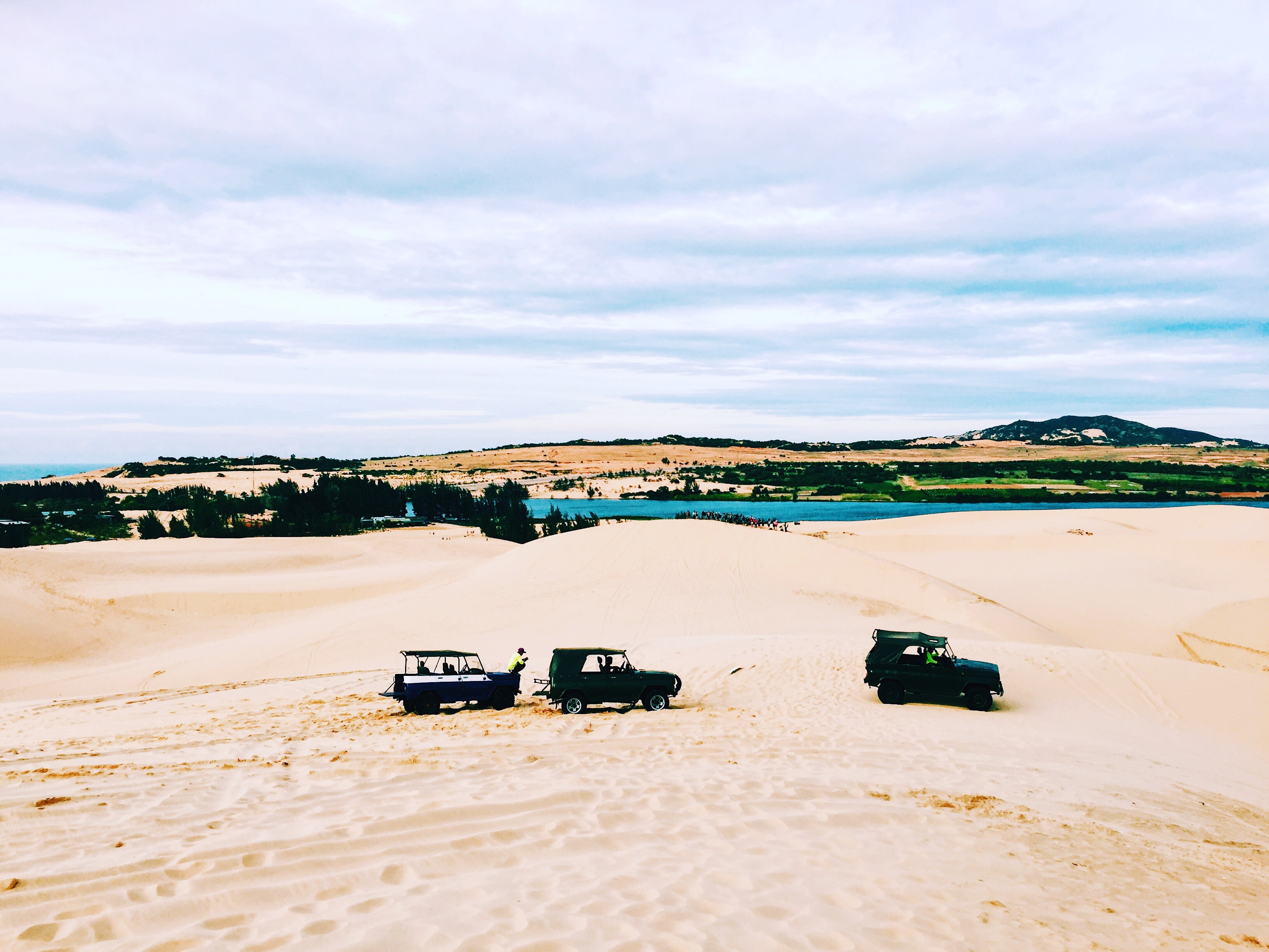 three off-road cars on white sand field during daytime