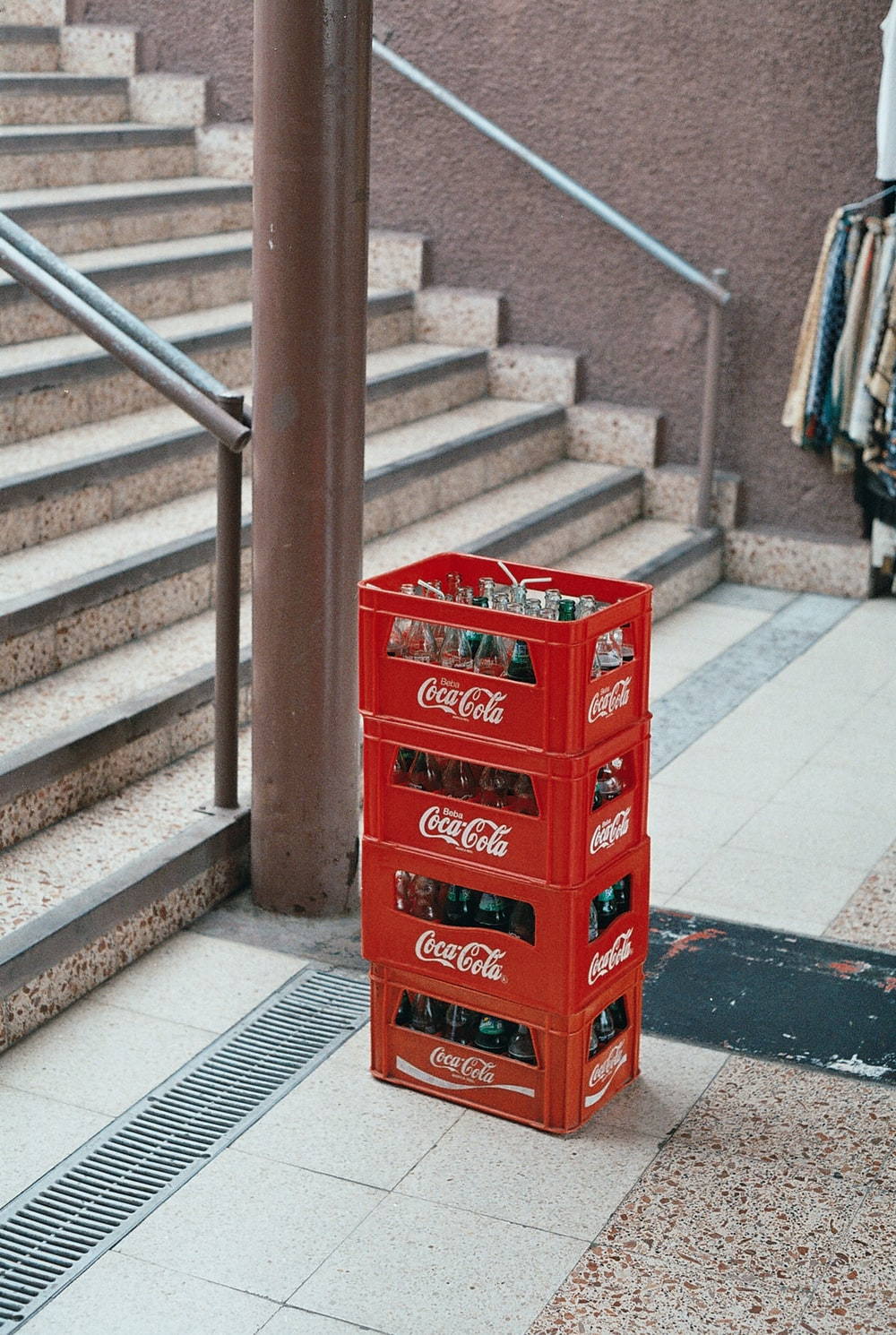 pile of four red Coca-Cola bottle crates near stairs