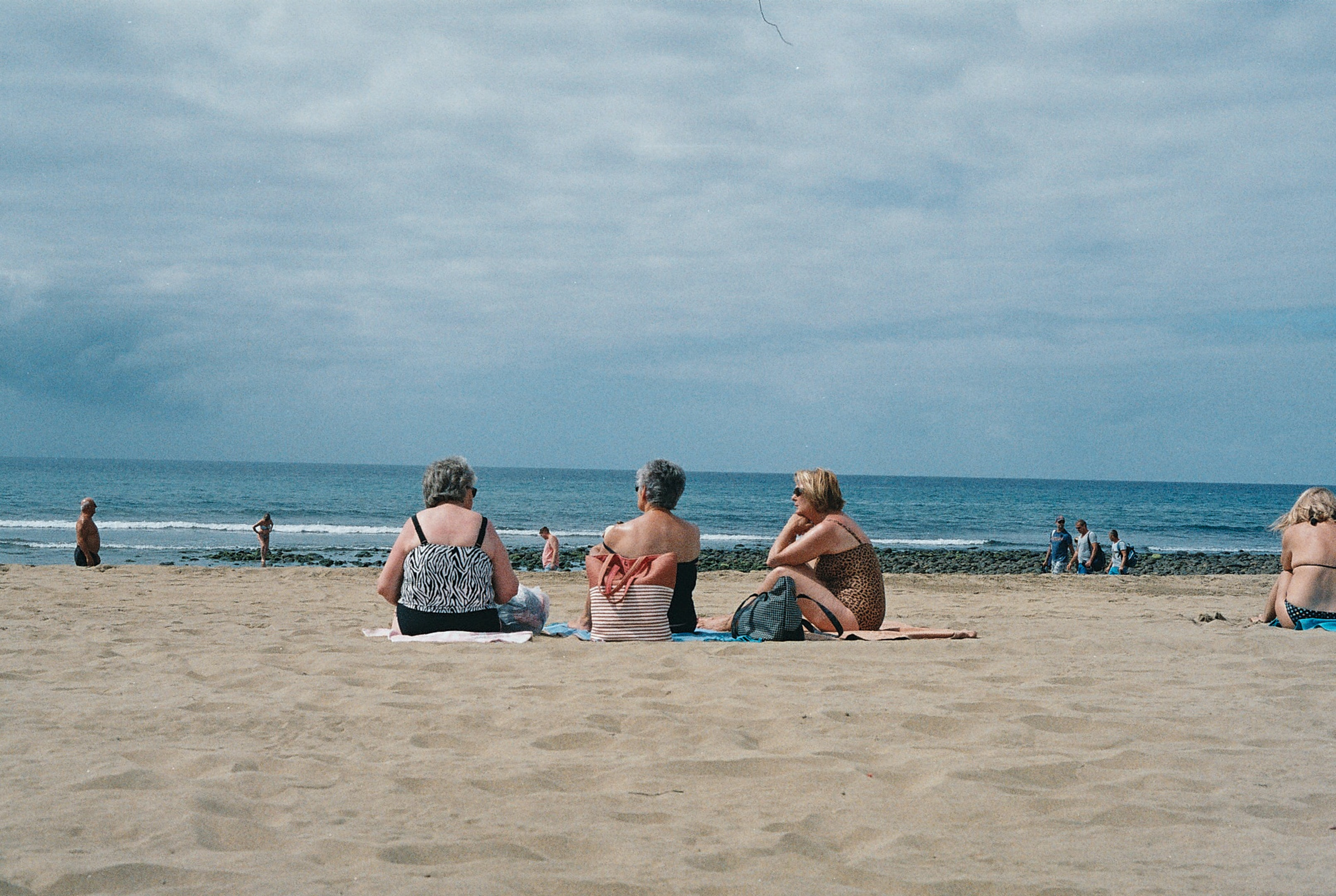 three women sitting on beach