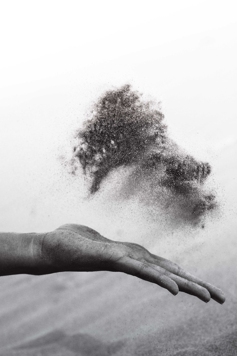 grayscaled photography of person's hand spreading sand