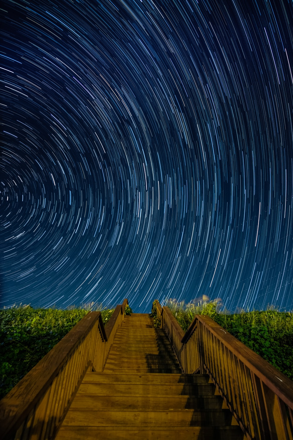 empty brown concrete stairs beside green grass under starry sky long-exposure photography