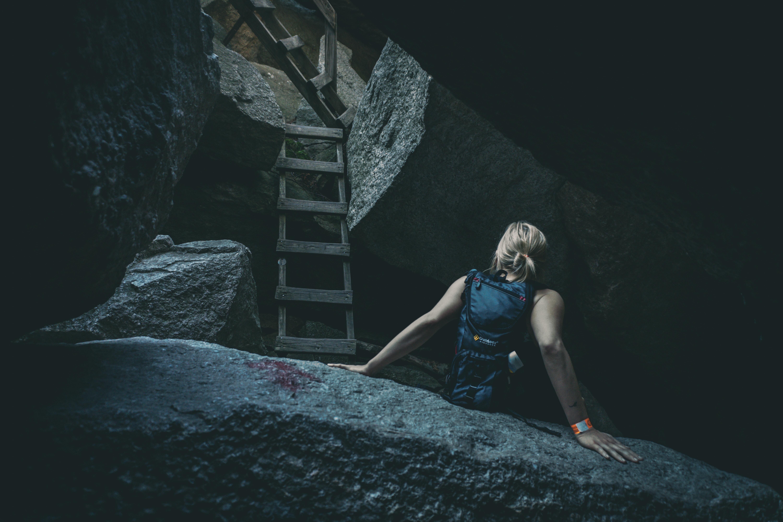 woman sitting of gray rock beside wooden ladder