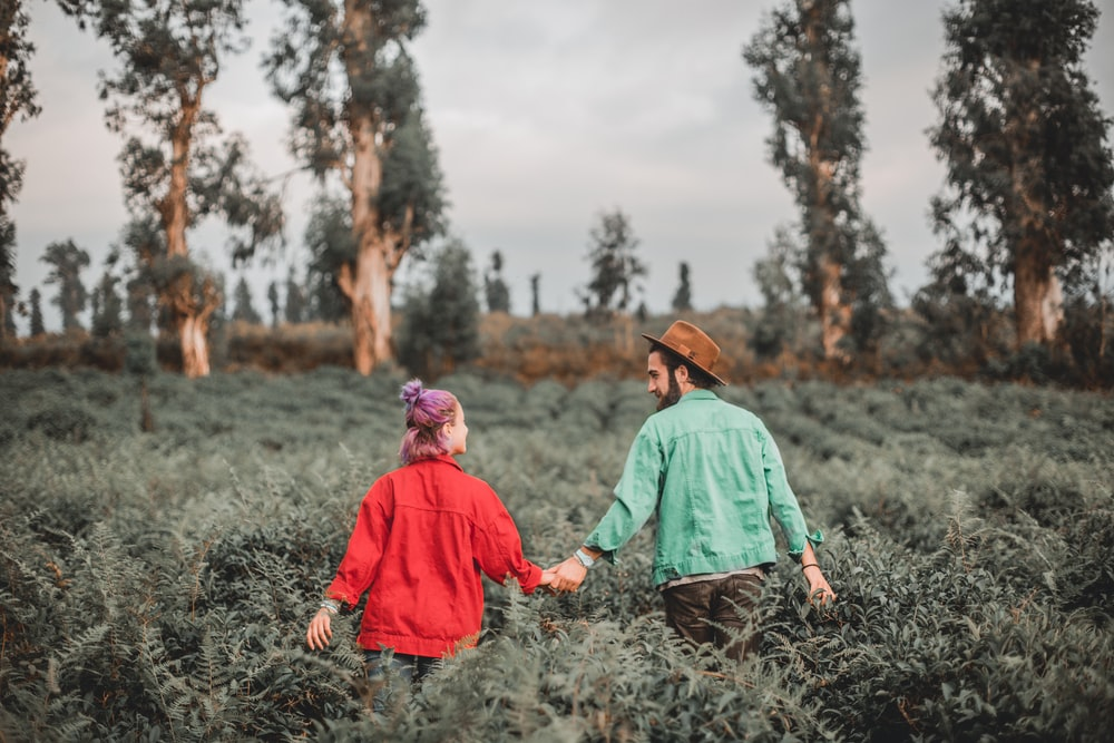 man and woman holding hands while walking on meadows