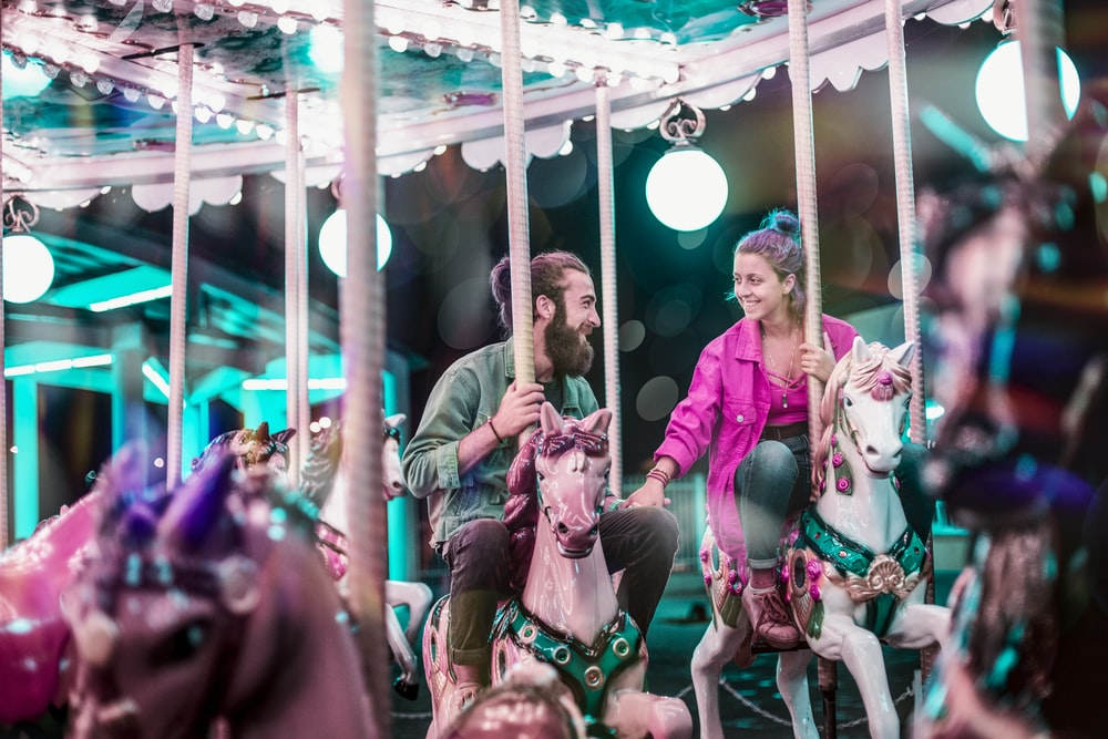 man and woman riding a carousel