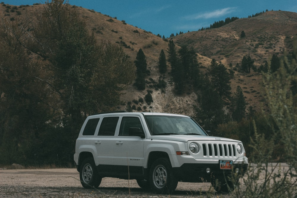 white Jeep SUV on brown soil at daytime