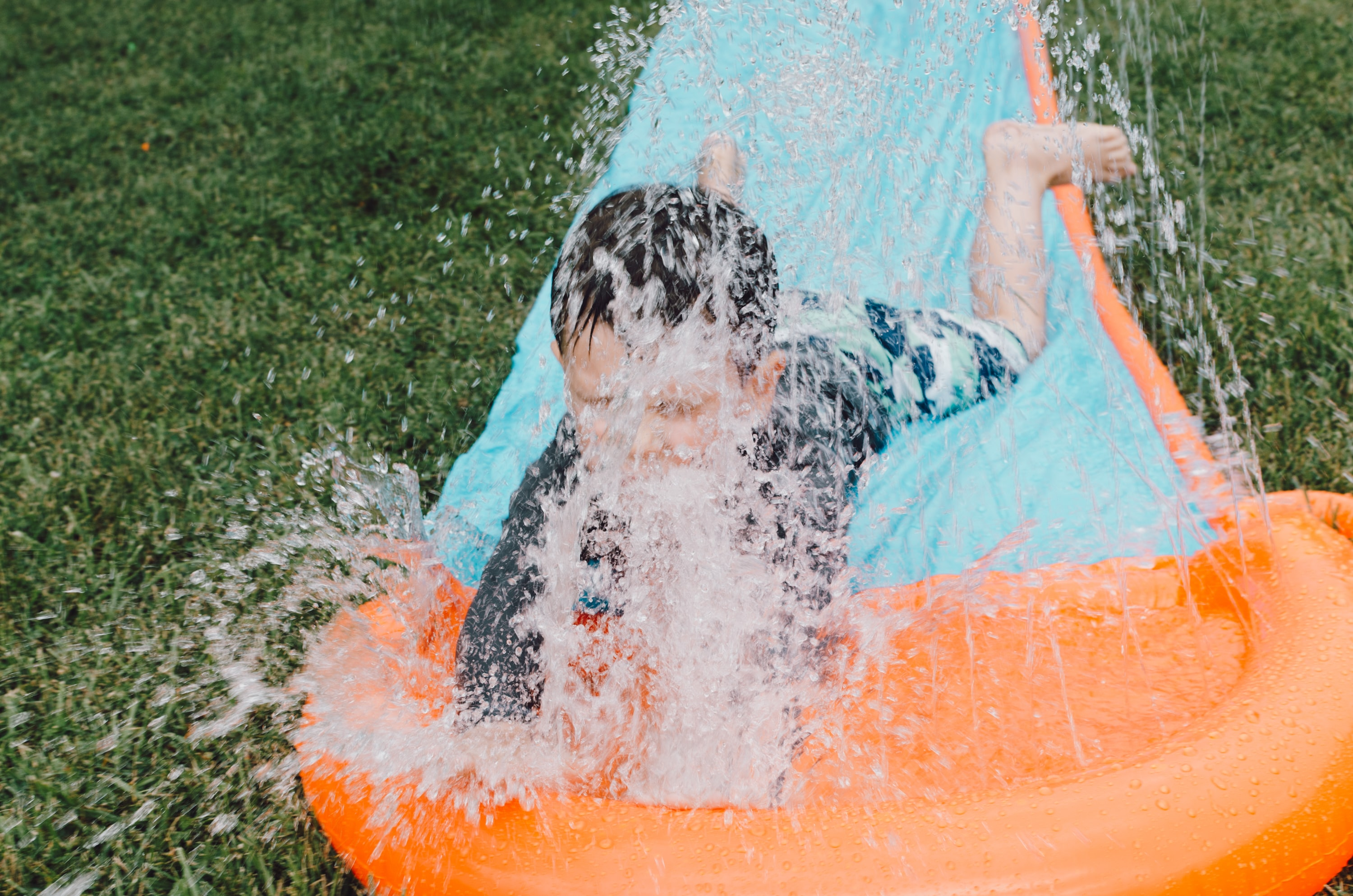 child sliding on blue and orange slippery pad with water splash at daytime