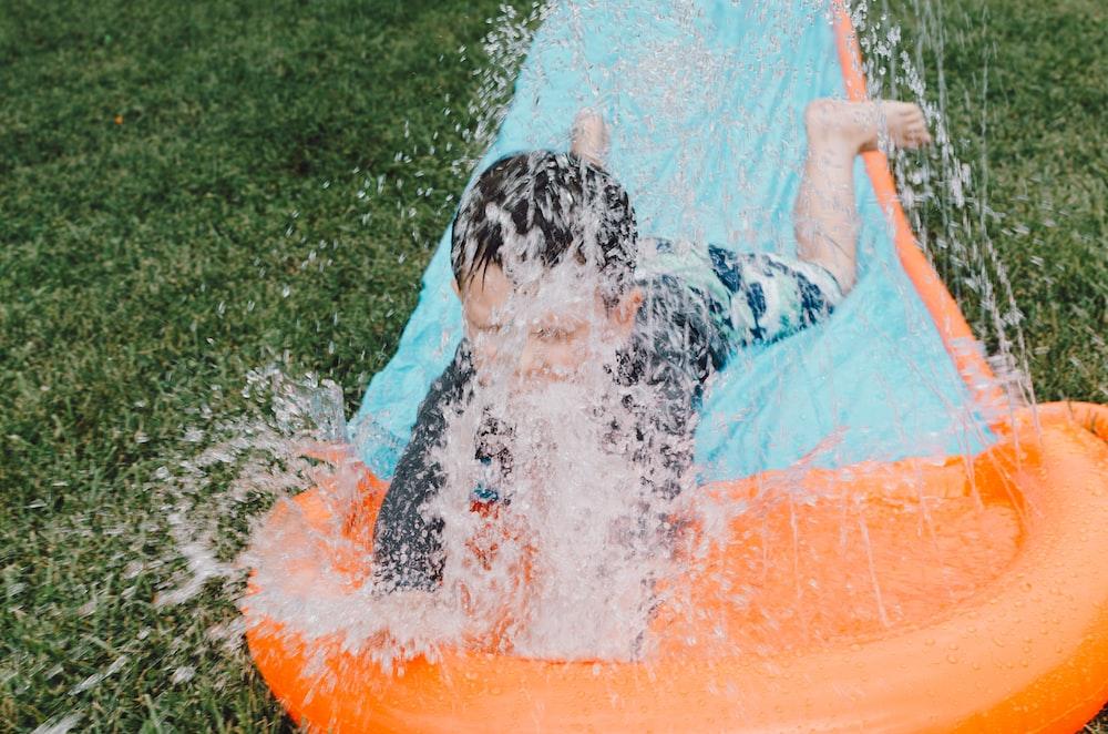 child sliding on blue and orange slippery pad with water splash at daytime