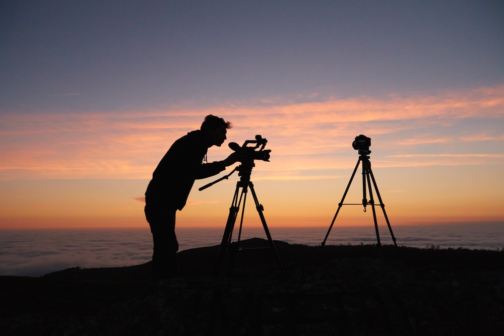 silhouette photo of person holding camera on tripod stand outside