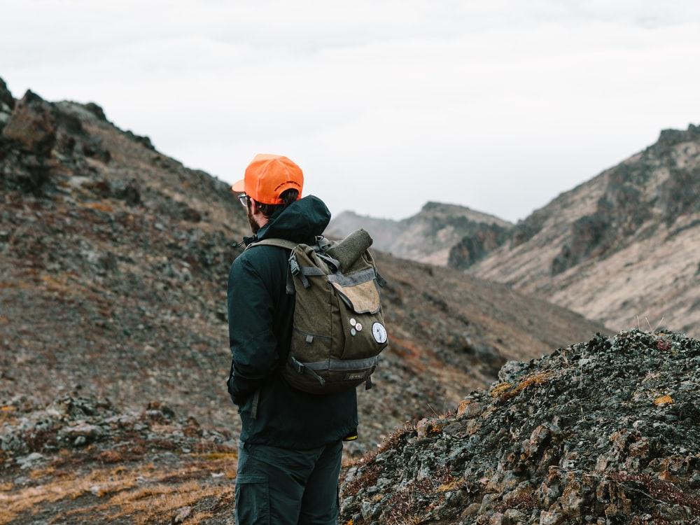man standing on grey mountain with backpack