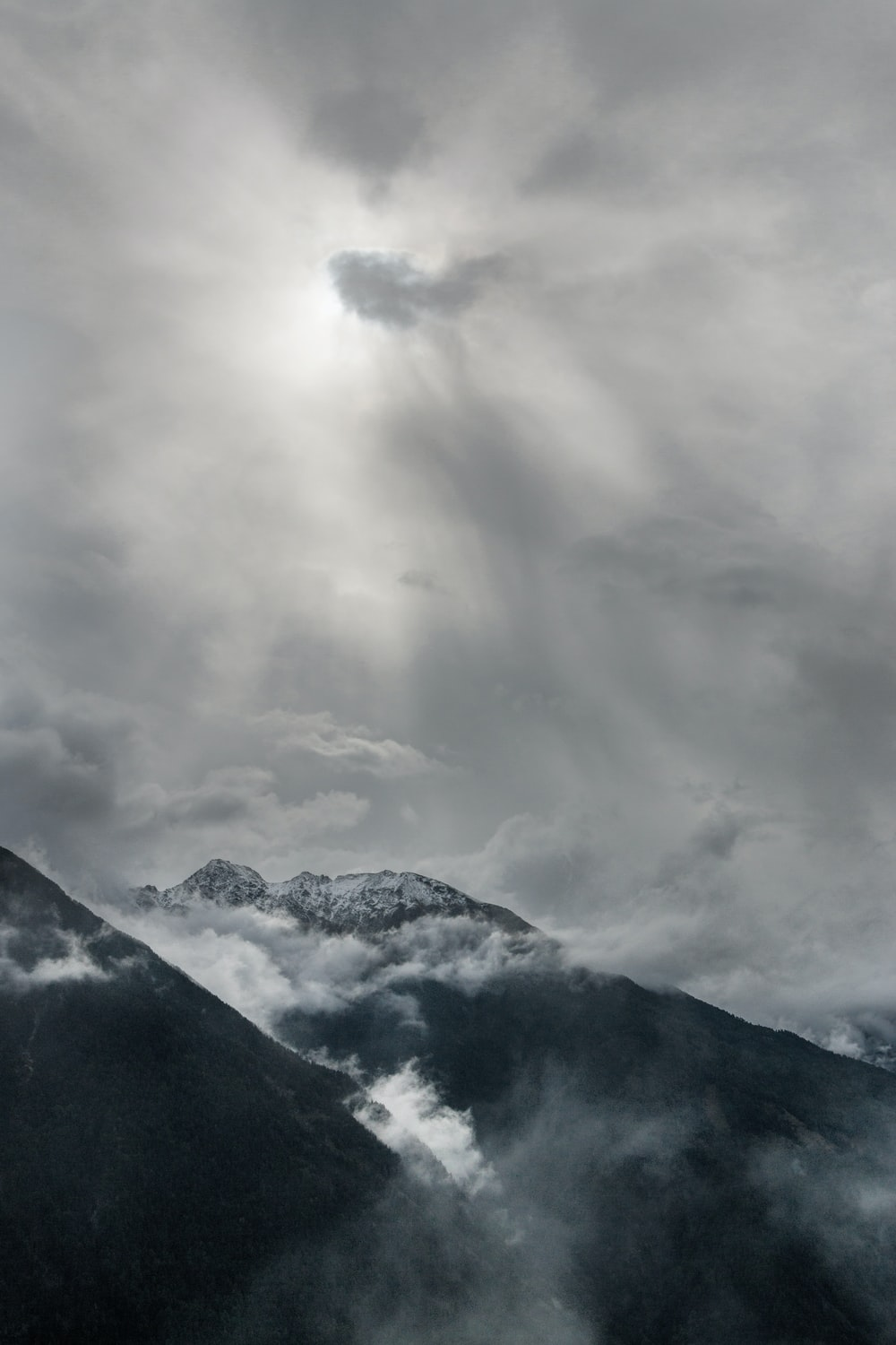aerial view of snowy mountains under cloudy sky