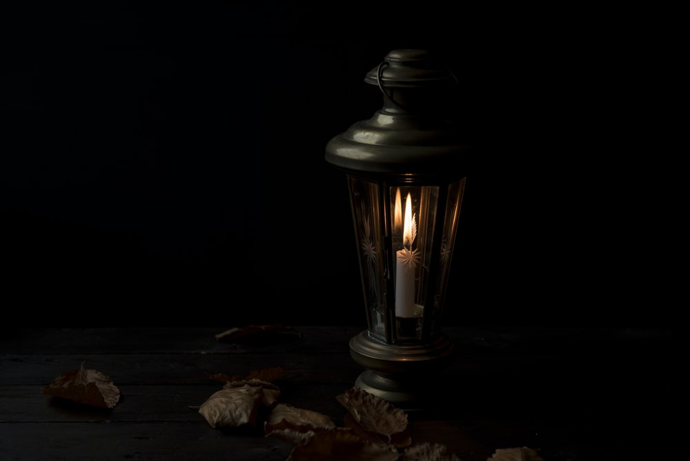 lighted lantern with dried leaves beside it