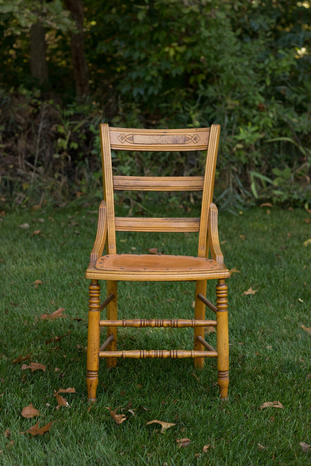 brown wooden chair on grass covered plain