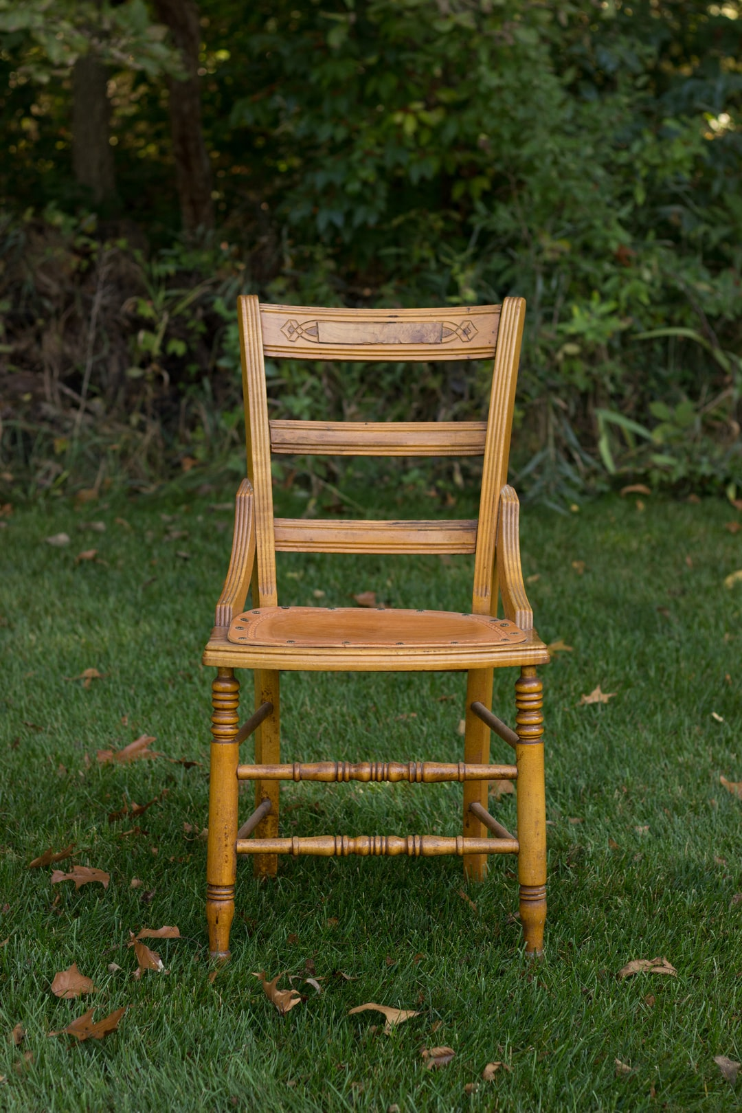 """I was getting some staging ready to take some newborn photos of my niece. This chair belonged to some of our ancestors. And it just looked so empty waiting there to be filled with the next generation. She is carrying on the name of two great-grandmothers just as we carry on using the chairs they used. The autumn season is just beginning, and those leaves tell a story of passing time, a change in a story."""