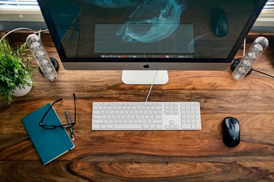 silver iMac near keyboard, mouse, and eyeglasses