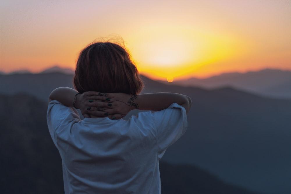 woman facing backward holding head facing sunset