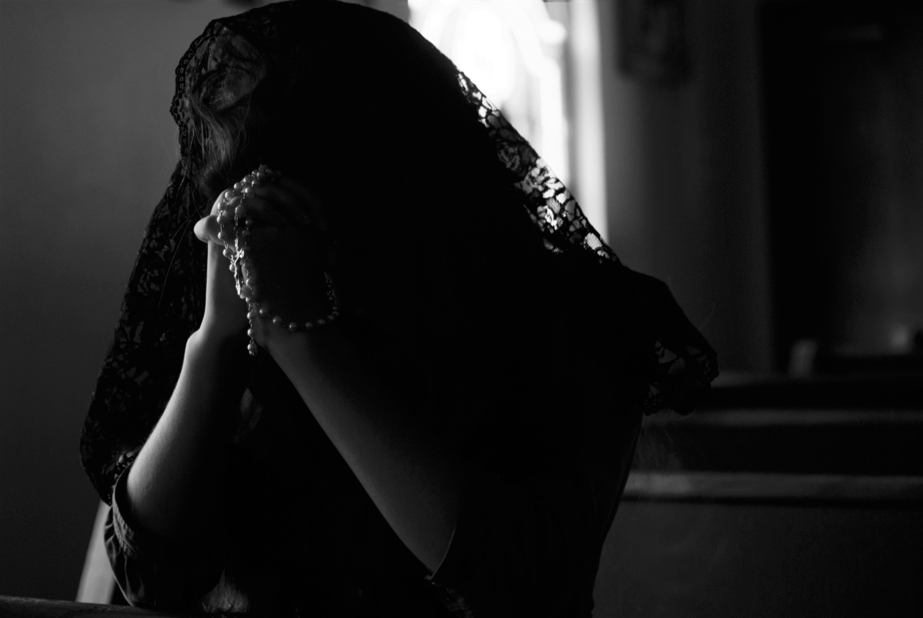 grayscale photography of woman praying while holding prayer beads