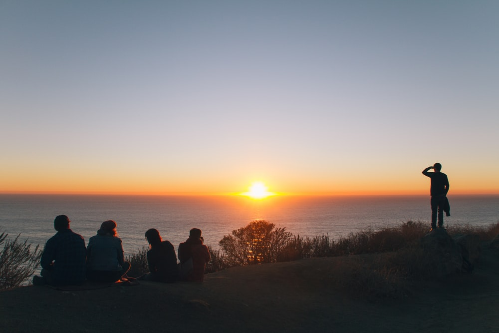 silhouette of people sitting and standing on hill near ocean at golden hour