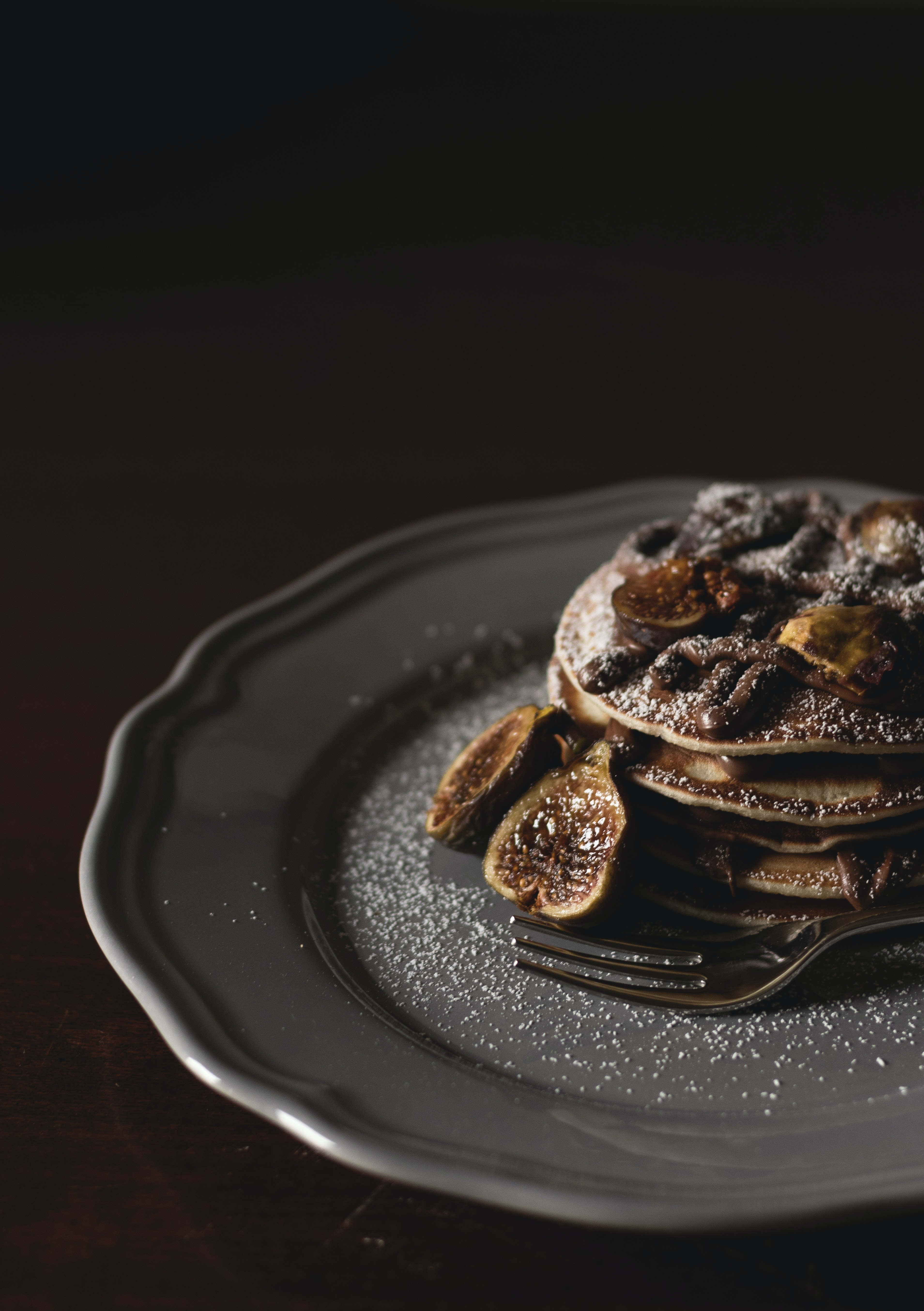 shallow focus photography of pan cakes with slices of banana and syrup on top on gray plate